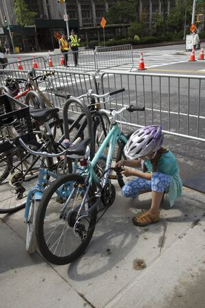 securing: Young cyclist locking her bicycle on the roadside, New York, USA