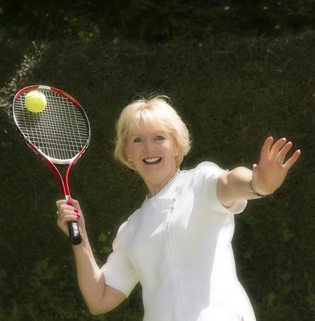 Elderly woman playing tennis