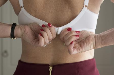 fastening: Elderly womans hands fastening her bra