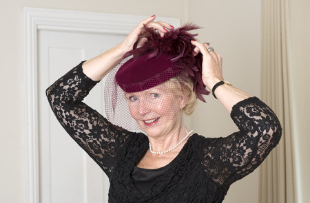 Elderly woman adjusting her maroon colored hat and veil with feathers