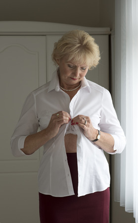 getting dressed: Elderly woman getting dressed putting on a white shirt