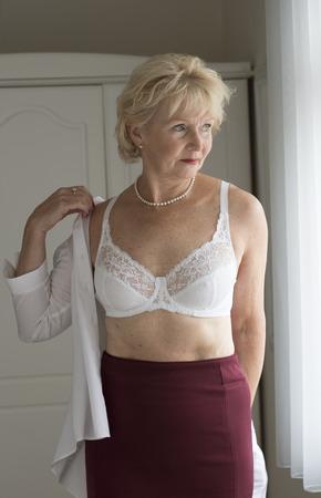 노인 여자는 흰색 셔츠에 넣어 옷을 입고하기 스톡 콘텐츠