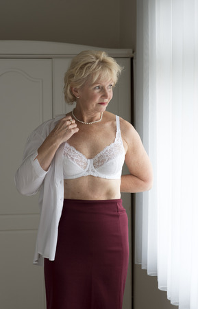 oap: Elderly woman getting dressed putting on a white shirt