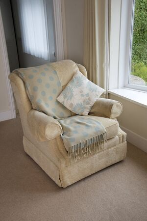 comfortable chair: A comfortable easy chair with cushion and shawl