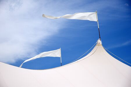 camping pitch: Marquee roof with flags blowing in the wind against a blue sky Stock Photo