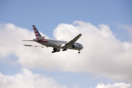 boeing: American Boeing 777 with landing gear down in preparation to land