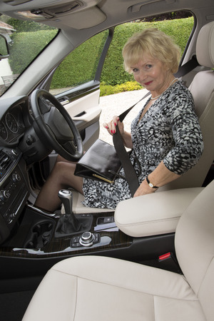 fastens: Elderly woman fastening the seatbelt in her car before driving