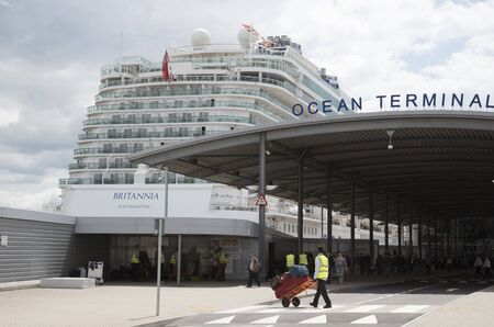 britannia: Cruise ship alongside Ocean terminal and porter with luggage Southampton UK Editorial