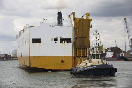 car carrier: Tug Svitzer Bargate with lines attached to car carrier Port Southampton England UK Editorial