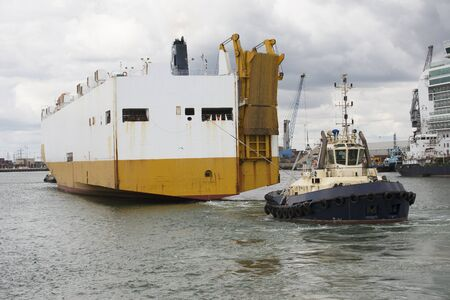 car carrier: Tug pulling a car carrier from the berth Editorial