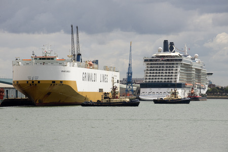 car carrier: Tugs moving a car carrier ship from its berth Port of Southampton England UK