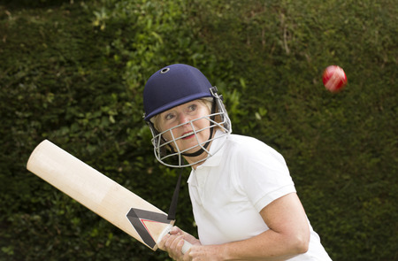 cricketer: Elderly woman cricketer wearing helmet playing cricket Stock Photo
