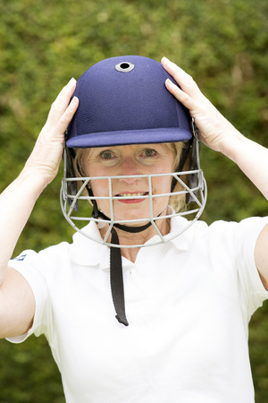 cricketer: Portrait of an elderly woman cricketer wearing a batswomans saftey helmet