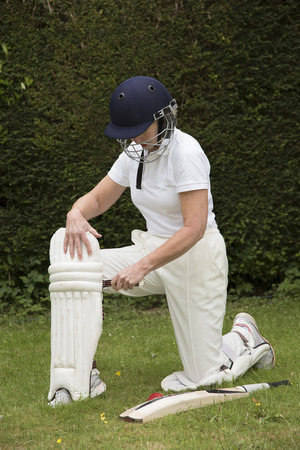 fastens: Elderly female cricketer fastens leg pads before going into bat
