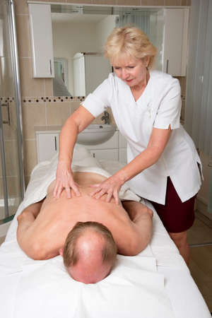 back rub: Masseuse working with a male client Providing a relaxing back massage