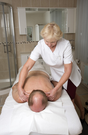 masseuse: Masseuse working with a male client Providing a relaxing back massage