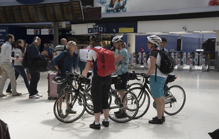 mingle: Passengers mingle on a busy London station concourse