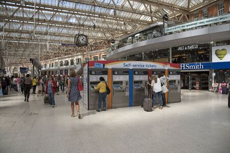 ticketing: Rail travellers purchasing railway tickets from a self service machine on station concourse
