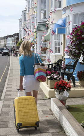 holidaymaker: Holidaymaker with suitcase looking for B&B accommodation at a seaside town Stock Photo