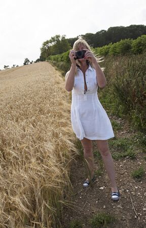 hobbyist: Woman in a white dress photographing a field of Barley Stock Photo
