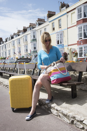 holidaymaker: Holidaymaker sitting on bench with B&Bs as the backdrop