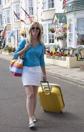 bb: Holidaymaker with suitcase looking for B&B accommodation at a seaside town Stock Photo