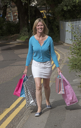 retail therapy: Woman walking in the street carrying her shopping
