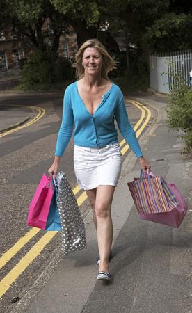Woman walking in the street carrying shopping bags