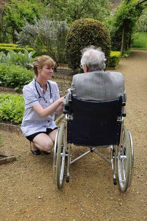 visitador medico: Cuidador enfermera atendiendo a paciente var�n de edad avanzada en una silla de ruedas Foto de archivo