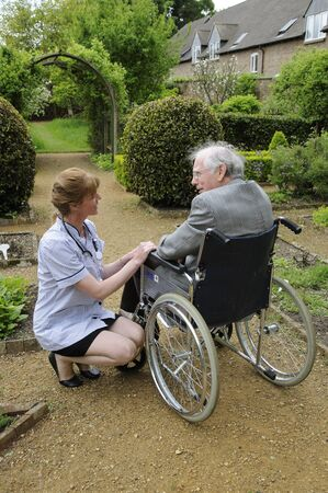 healthcare visitor: Carer wheeling a elderly man in a wheelchair in a garden