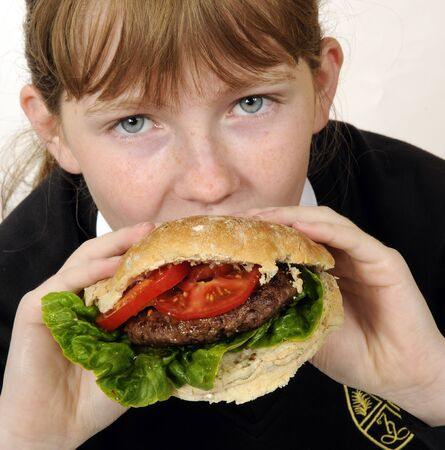 beefburger: Schoolgirl eating a beefburger with a healthy salad filling