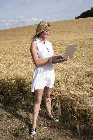surveying: Woman in white dress and laptop computer surveying field of barley