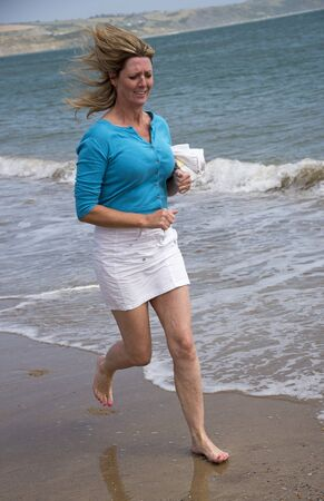holidaymaker: Woman running along the beach to keep fit