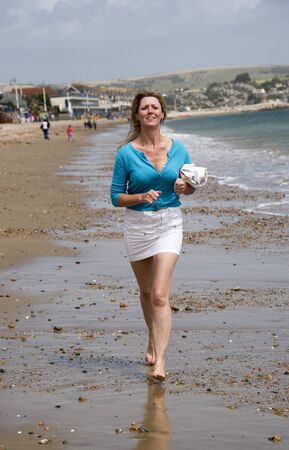 keep fit: Woman running along the beach to keep fit