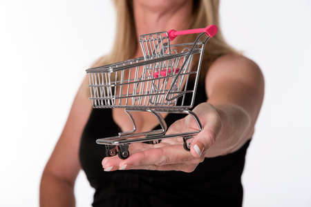retail therapy: Woman holding tiny supermarket trolley