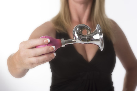loud noise: Woman holding a small hooter for making a loud noise Stock Photo