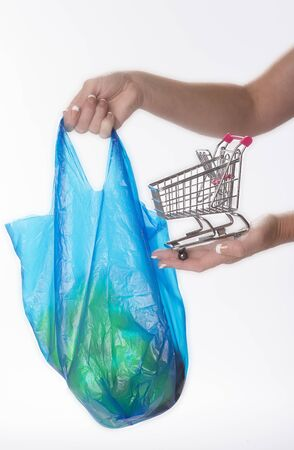 rising prices: Woman holding tiny supermarket trolley and plastic shopping bag
