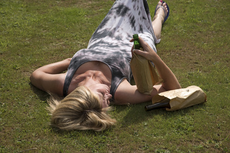 boozer: Woman laying on grass holding bottles of beer covered with brown paper bags Stock Photo