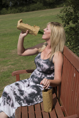 boozer: Woman drinking alcohol with bottle in brown paper bag in a public place