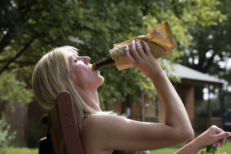 tomando alcohol: Woman drinking alcohol with bottle in brown paper bag in a public place