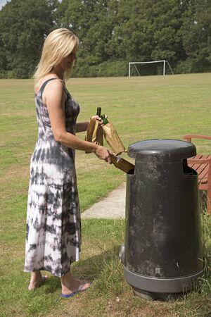 boozer: Woman disposing of empty beer bottles in litter bin Stock Photo