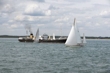 entries: SS Shieldhall a historic steam ship with the yacht Stormey Weather of Cowes 115 and GBR1010 Xinski entries in Rolex Fastnet Race entry on The Solent off Cowes UK