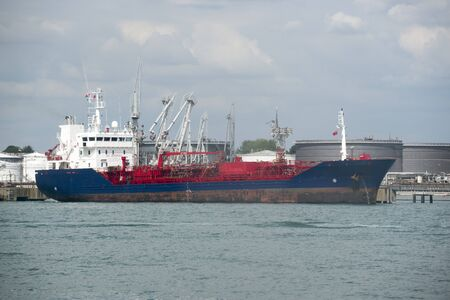 Oil tanker ship unloading its cargo of fuel to storage tanks