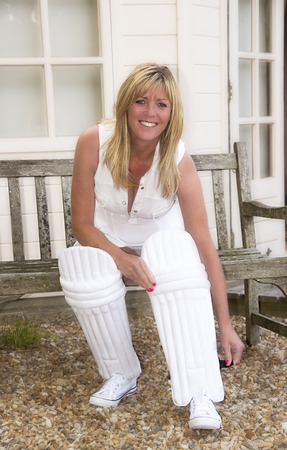 putting on: Woman putting on her cricket pads outside the pavilion