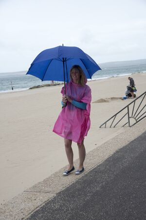 holidaymaker: Holidaymaker with an umbrella and poncho at the seaside on a wet day