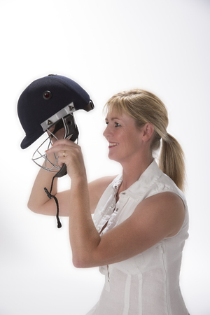 cricketer: Portrait of a woman cricketer adjusting her safety helmet