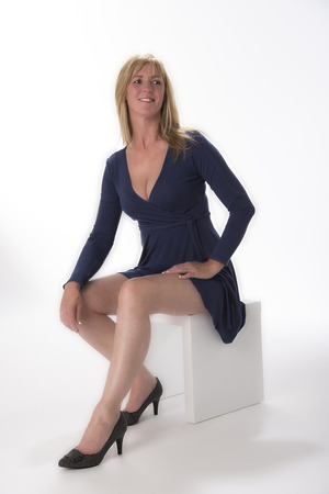 neckline: Woman sitting in a blue dress with a low neckline Stock Photo