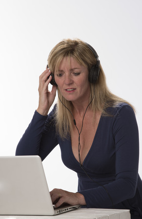 late forties: Woman in a blue dress wearing headphones and working on a laptop