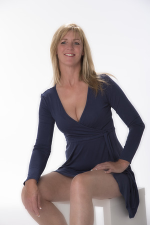 Woman sitting in a blue dress with a low neckline Stock Photo