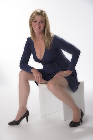 donne mature sexy: Donna seduta in un vestito blu con una scollatura Archivio Fotografico